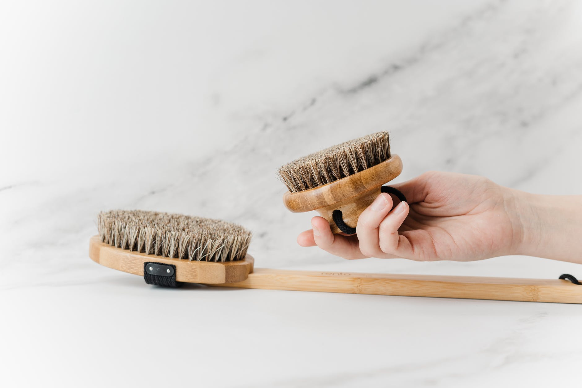 person holding brown wooden brush