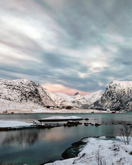 snow covered mountain near lake under cloudy sky