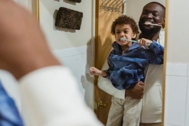 black father and son brushing teeth in bathroom