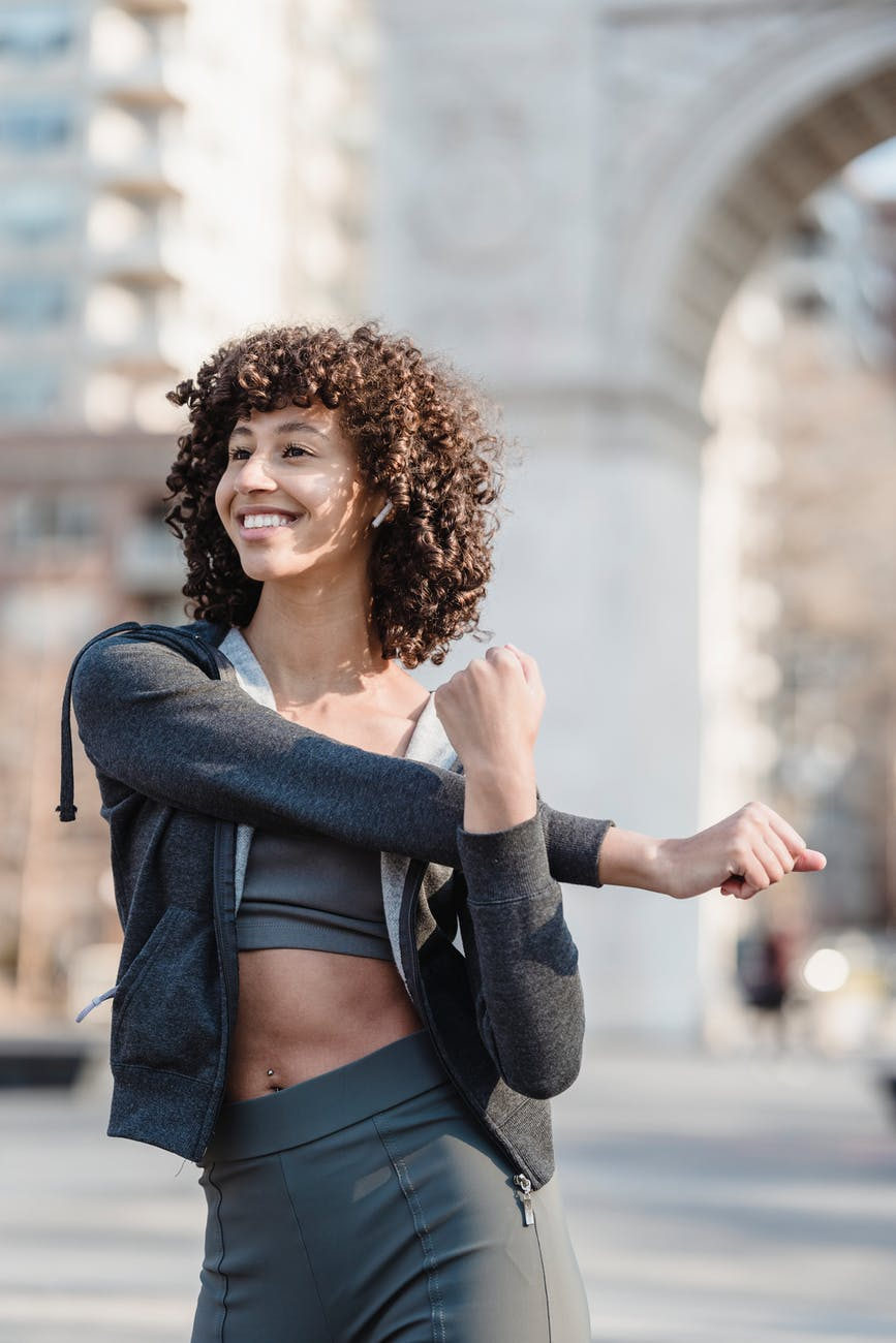 smiling fit ethnic woman in earbuds warming up before training